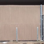 10-foot galvanized chain link fence with privacy slats and ballards