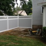 Grey and white two-tone lattice topped vinyl fence with New England caps